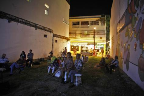 In this Sept. 21, 2014 photo, people watch a movie at a makeshift outdoor movie theater in the Santurce neighborhood in San Juan, Puerto Rico. Outdoor movie nights are held in an empty lot in a spot named Cinema Paradiso created by filmmaker Michelle Malley Campos. (AP Photo/Ricardo Arduengo)